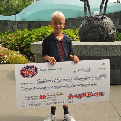 Michael Stanley, cancer survivor, with donation check from Jersey Mike's Middle Tennessee Co-op.