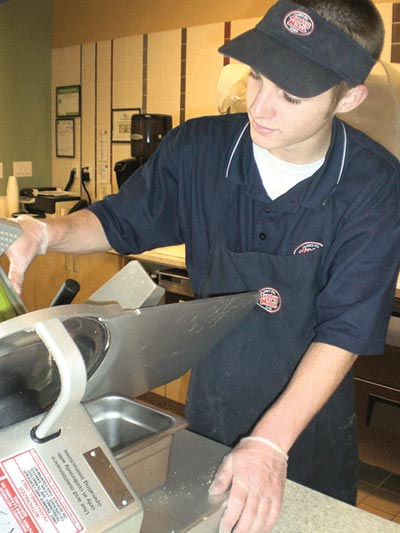 Jersey Mike's employee Zach Otto slices fresh ingredients.