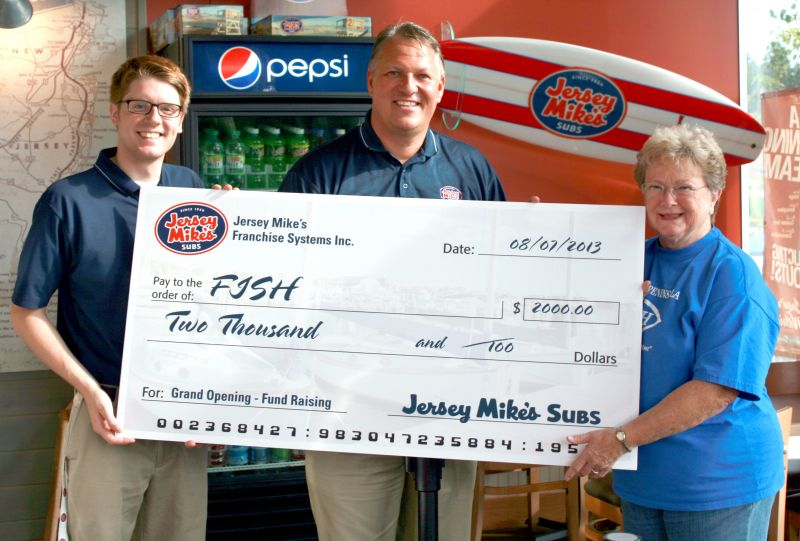 Jeff Gates, owner of Jersey Mike's Subs in Uptown Gig Harbor, and assistant manager Ryan Curlett donate a check to Jan Coen, president of the Gig Harbor/Peninsula FISH Food Bank.