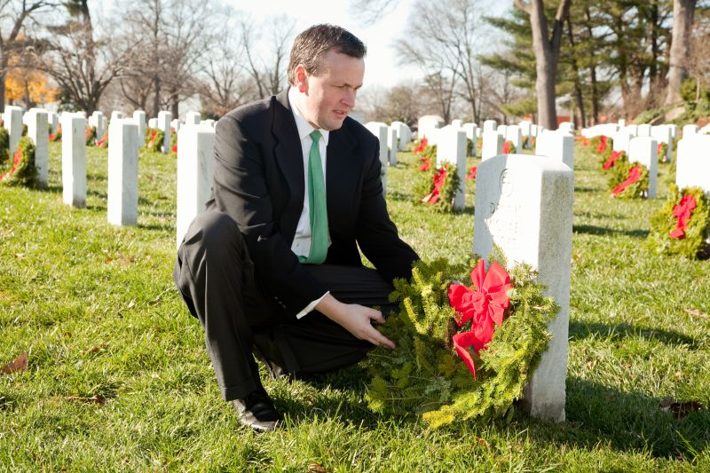 Franchise owner Danny Malamis places a wreath on a grave in Arlington National Cemetery December 2012.