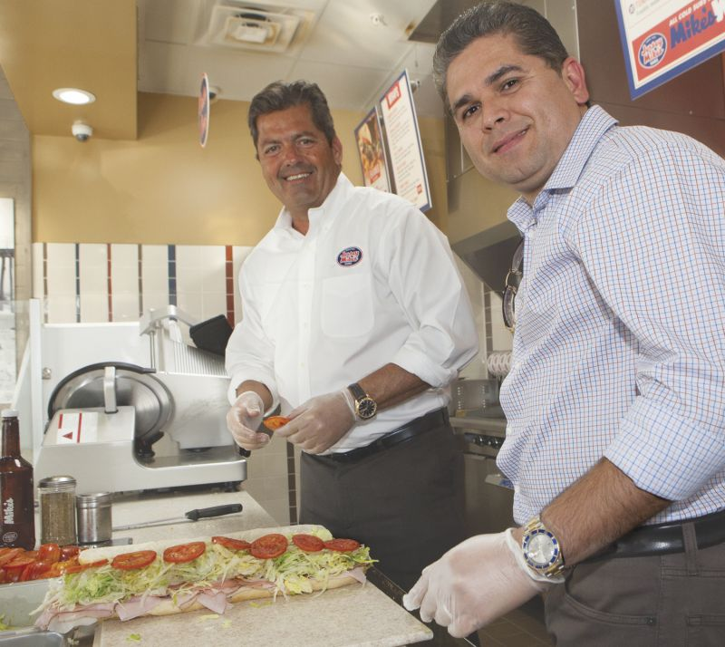 Dan Burrell, left, area manager and store director for Jersey Mike's Subs, and Alvaro Garcia, owner of 60 franchise locations open and in development, team up on preparing a freshly made sub sandwich at the Garcia's shop at Douglas Park in Long Beach. Two of Garcia's Jersey Mike's Subs stores are in Long Beach, with two more for the