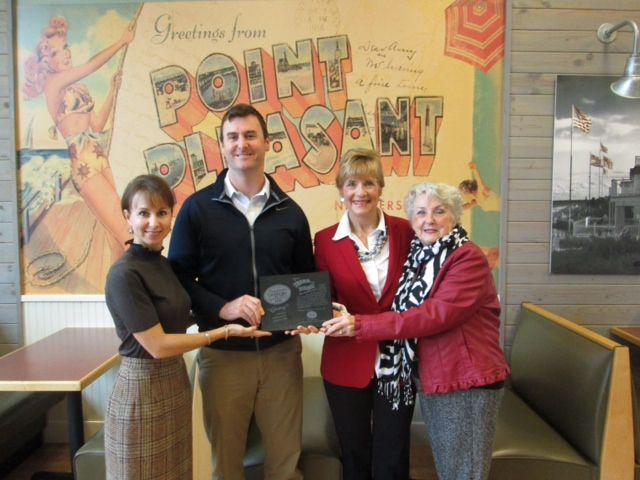 Dalton Stewart, Jersey Mike's Subs Dallas/Forth Worth area director, presents a plaque to (l. to r.) Evelyn Costolo, Wipe Out Kids' Cancer (WOKC) CEO, Cindy Brinker, WOKC founder, and Mary Dowling, WOKC advisory board member, recognizing the Dallas-based organization as one of 14 charities featured on Jersey Mike's beverage cups nationwide.